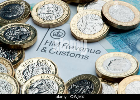 An HM Revenues & Customs letterhead surrounded by new £1 coins and a £5 note. - Stock Photo