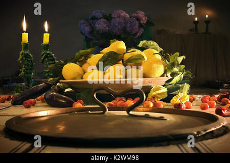 BEAUTIFUL STILL LIFE WITH CANDLES, LEMONS, CHERRIES FLOWERS IN A LOVELY SETTING OF AN ANTIQUE KITCHEN IN ITALY. - Stock Photo