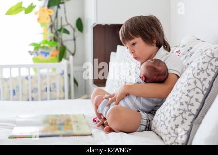 Sweet preschool boy, reading a book to his newborn brother, sitting on the bed in bedroom, childhood concept - Stock Photo