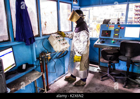 Man wearing a protective gear operating a machine in a metallurgy plant. Guaramirim, Santa Catarina, Brazil. - Stock Photo