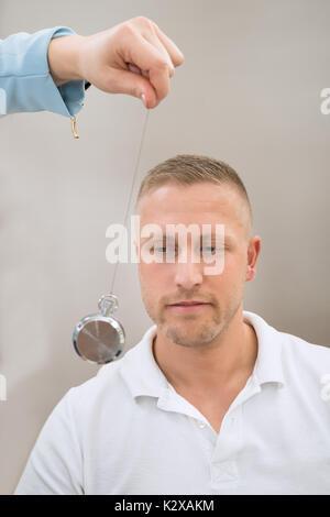 Close-up Of Psychiatrist Hypnotizing Young Man With Pendulum - Stock Photo
