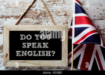a wooden-framed chalkboard with the question do you speak English? written in it and a flag of the United Kingdom - Stock Photo