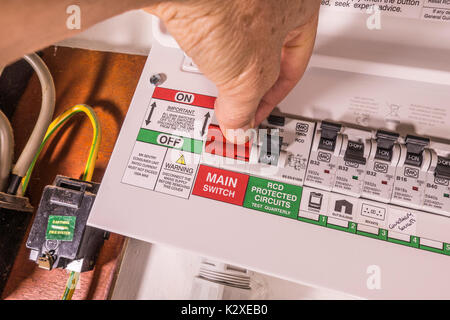 Man's finger and thumb on the main on/off switch of a newly fitted electricity consumer unit, with multiple switches. - Stock Photo