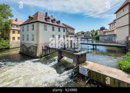 Bamberg, Germany - May 22, 2016: Dams, bridges, old houses on artificial islands and banks of the Regnitz river. - Stock Photo