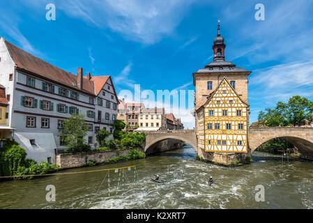 Bamberg, Germany - May 22, 2016: Historical city hall of Bamberg on the bridge across the river Regnitz and kayaking - Stock Photo