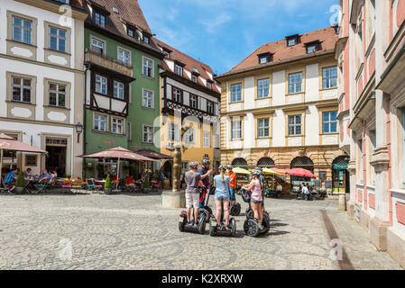 Bamberg, Germany - May 22, 2016: Tourists on segways visiting Bamberg old town Pfahlplatzchen square in Upper Franconia, - Stock Photo