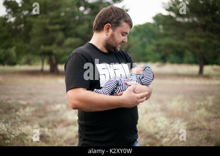 Happy father stands and holds his sleeping newborn baby in hands on walk. - Stock Photo