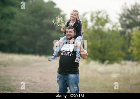 Happy father with daughter smile on walk in park. Dad put child girl on his shoulders. - Stock Photo
