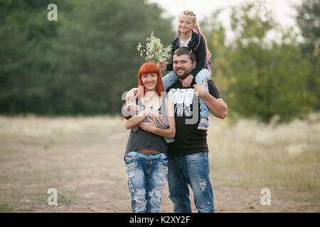 Happy young family with two children on walk in park. Mother holds her newborn son in hands, and father put daughter - Stock Photo
