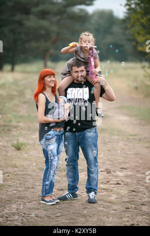 Happy young family with two children blowing soap bubbles on walk in park.  Mother holds her newborn son in hands, - Stock Photo