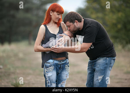 Happy young family with newborn baby on walk in park. Mother holds in her hands newborn baby, father stands near - Stock Photo