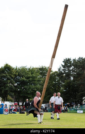 Ballater, Scotland - Aug 10, 2017: A competitor in the caber toss, a traditional Scottish Highland Games event, - Stock Photo
