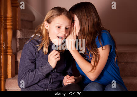 Two girls sat on the stairs at home with one whispering a secret to the other. - Stock Photo