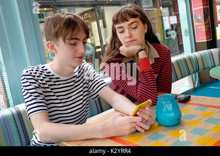 young teenage couple in urban cafe using mobile phone