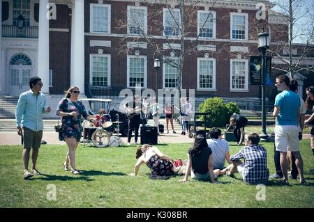 Students walk with drinks and sit on the grass to enjoy a student band playing in front of Gilman Hall, during Spring - Stock Photo