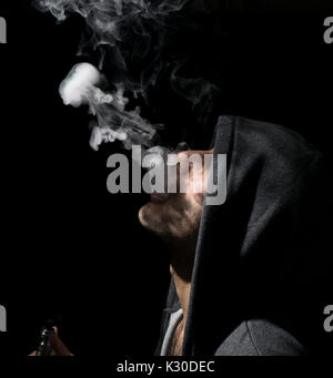 Isolated man doing a jellyfish trick of vaping and electronic cigarette. - Stock Photo