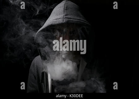 vaping man wearing a hoody with lots of smoking clouds. - Stock Photo