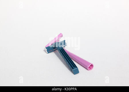 A blue Schick disposable & pink Bic disposable razor both made from the plastic, polypropylene. - Stock Photo