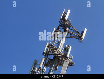 The top of a communications cellular tower stands out against a clear blue sky. - Stock Photo