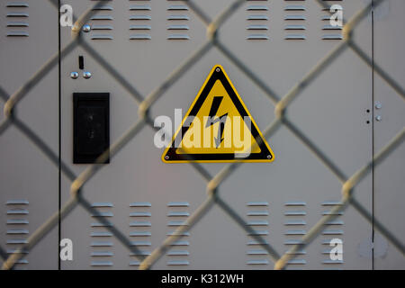 electrical hazard sign placed on a electric power substation behind a metal fence of wire mesh - Stock Photo