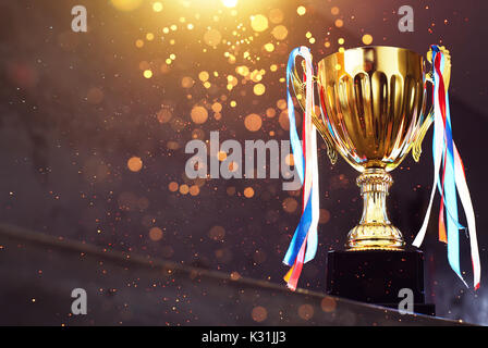 Low key golden trophy on the blur gray background with abstract shiny lights .