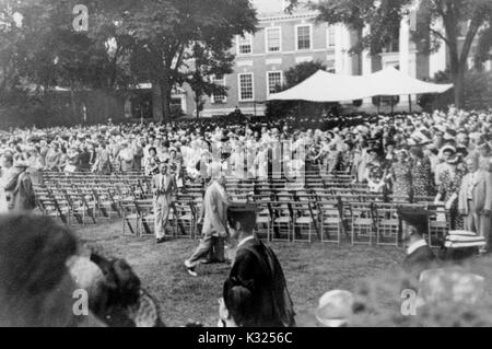 On Commencement Day, a crowd of parents and guests stand outside behind chairs lined up in rows on the quadrangle - Stock Photo