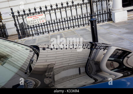 Railings and an embassy wall reflected in the polished bonnet (hood) of a diplomatic BMW car in Queen's Gate Terrace - Stock Photo