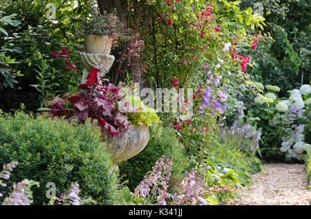 Fountain with alumroots (Heuchera) and plantain lilies (Hosta). Design: Marianne and Detlef Lüdke - Stock Photo