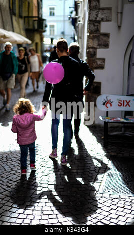 A mother and daughter walking through Bolzano, Italy - Stock Photo