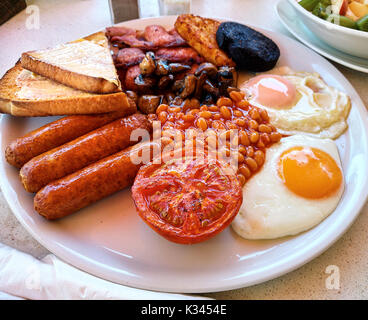Traditional full english breakfast. Fried eggs, baked beans, bacon, sausages and toasts - Stock Photo