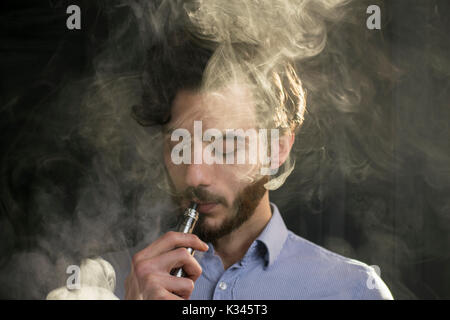 young man vaping electronic cigarette, e cigarette, e cig with smoke clouds. - Stock Photo