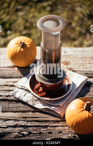 Autumn outdoor coffee picnic. Coffee cups, cute little pumpkin on the old table background - Stock Photo
