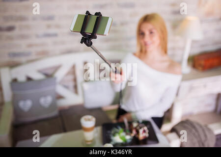 A photo of young woman making herself a photo with her smartphone. - Stock Photo