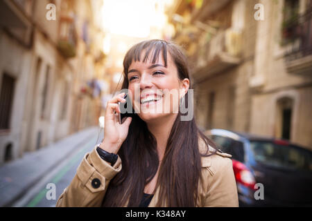 A photo of young, beautiful woman talking on the mobile and laughing. - Stock Photo