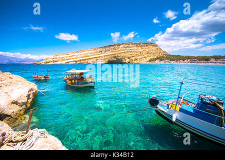 Matala beach with caves on the rocks that were used as a roman cemetery and at the decade of 70's were living hippies - Stock Photo