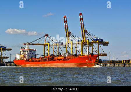 Red freight ship in front of port facilities and cranes - Stock Photo