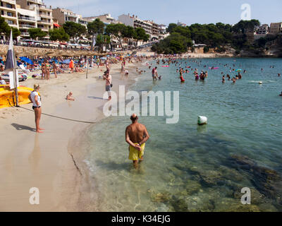 Tourists relax on the beach in Porto Christo with clear water to enjoy. - Stock Photo