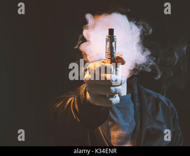 Isolated young man on a black background holding an electronic cigarette, vaping device, mod. - Stock Photo