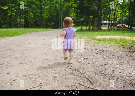 A toddler walk away from the camera down a dirt path. - Stock Photo