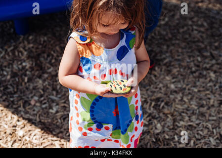 A little girl looking at a painted rock she is holding - Stock Photo