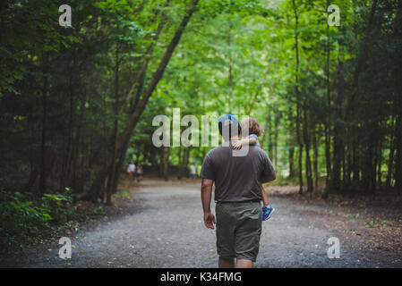 A father carries his daughter along a tree covered trail. - Stock Photo