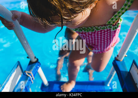 A young girl climbs out of a swimming pool during  the summer. - Stock Photo