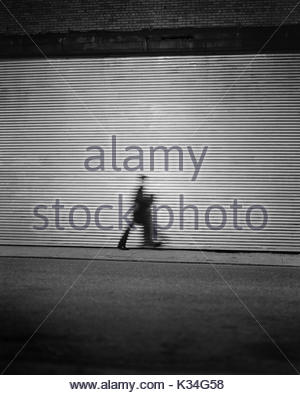 Blurred Silhouette of Man Walking in front of Corrugated Garage Door - Stock Photo