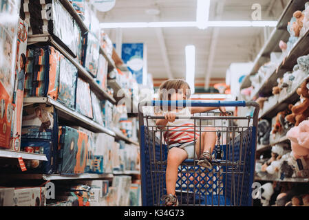 A toddler sits in a shopping cart in a toy store. - Stock Photo
