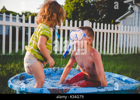 A boy wearing a scuba mask looks at a little girl in a kids swimming pool - Stock Photo