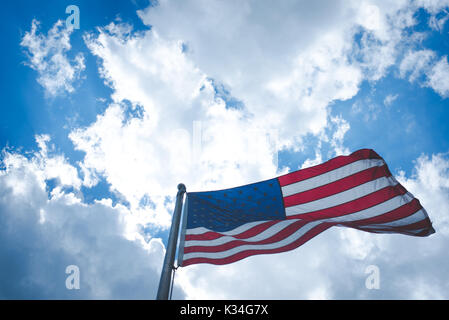 An American flag blows in the wind against a blue sky with clouds. - Stock Photo