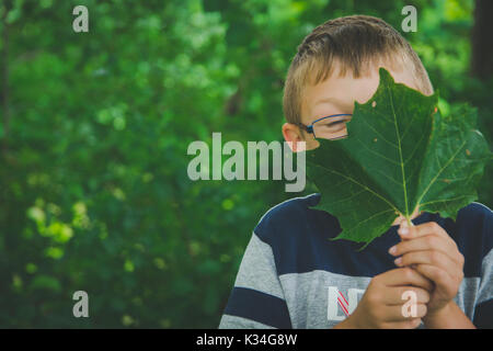 A young boy holds a green leaf in front of his face. - Stock Photo