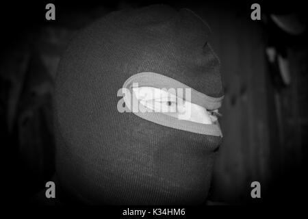 Criminal Male Terrorist with black mask, masked burglar - Stock Photo