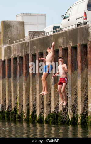 Two teenage boys jump off the pier into the sea in Schull, West Cork, Ireland. - Stock Photo