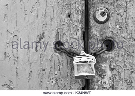 Padlock and chain protecting the entrance of an old colonial heritage. building - Stock Photo